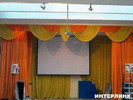 Экран с электроприводом Classic Lyra в актовом зале школы
