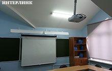 Рулонный настенный экрана и мультимедийный проектор в учебном классе